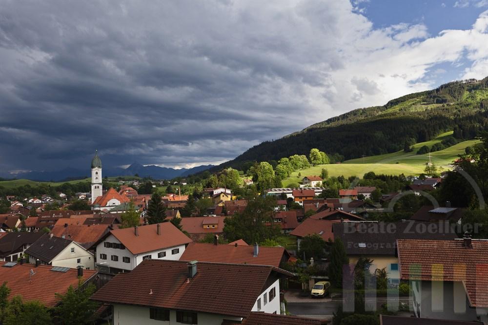 Sommerliche Gewitterfront über der Stadt Nesselwang im Ostallgäu, im Hintergrund die Berge der Alpen