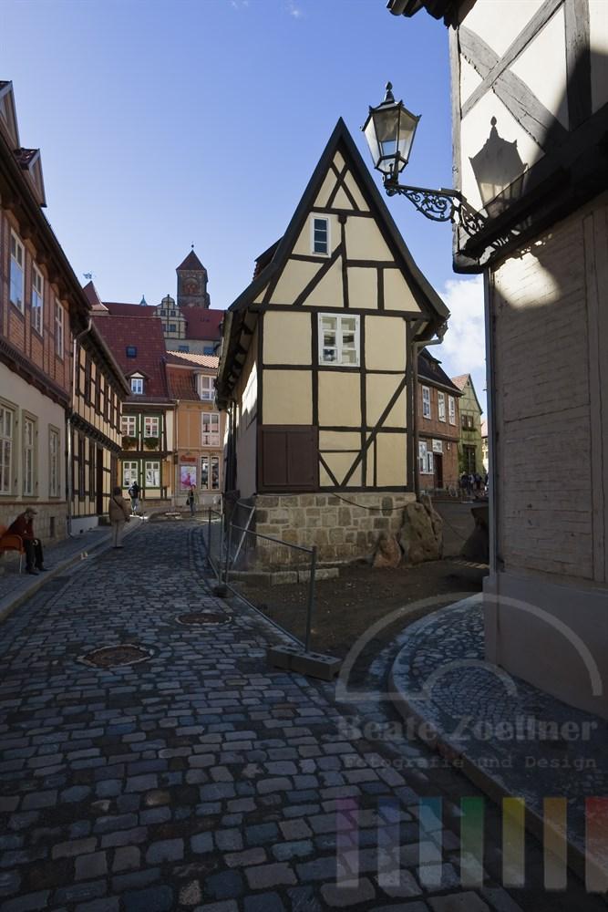 Strasse in Quedlinburg mit historischen Fachwerkhäusern. Im Hintergrund auf dem Schlossberg die Stiftskirche St. Servatius