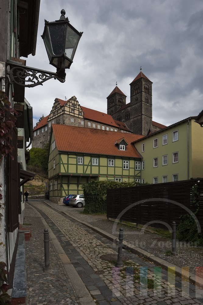 Blick aus einer Gasse auf das Wahrzeichen der mittelalterlichen Stadt Quedlinburg: Die Stiftskirche auf dem Schlossberg - Himmel bedeckt, dunkle Wolken