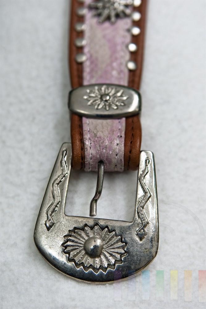 close: silberne Schnalle an einem Lederguertel, Hintergrund weiß