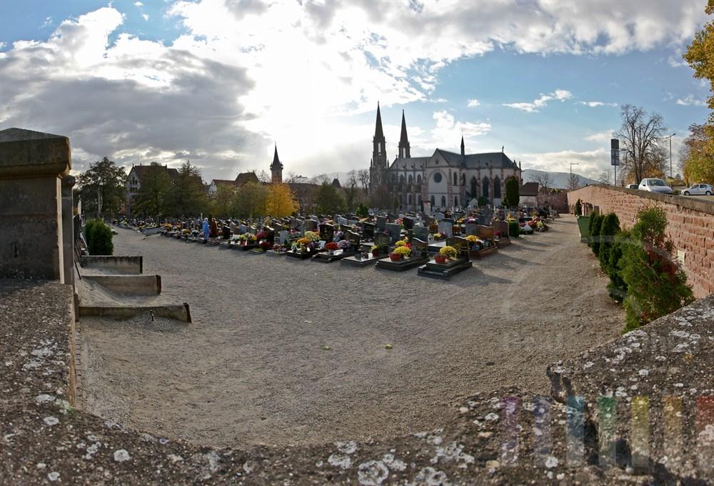 Friedhof in Obernai/Elsass. Im Hintergrund die Kirche St. Peter und Paul, dahinter die Vogesen