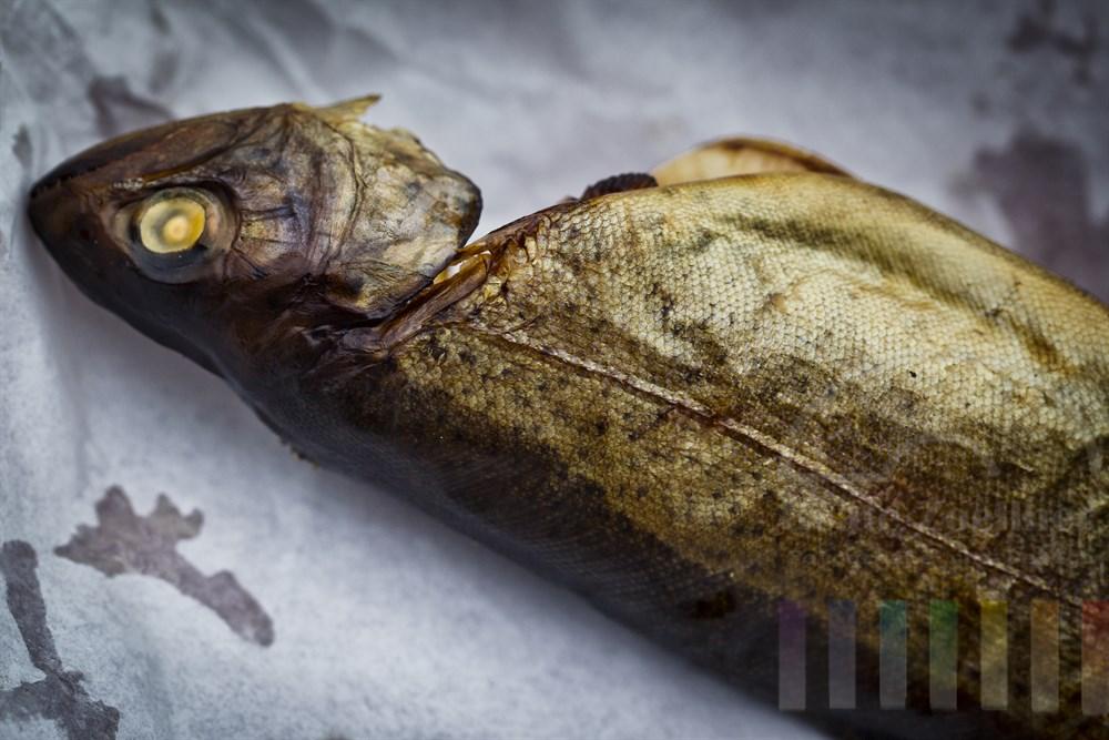 geräucherte Forelle liegt verzehrbereit auf einem Stück Pergamentpapier