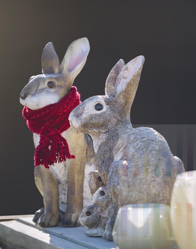 Häschen-Figuren aus Stein als Oster-Dekoration. Vater Hase trägt einen roten Schal um den Hals