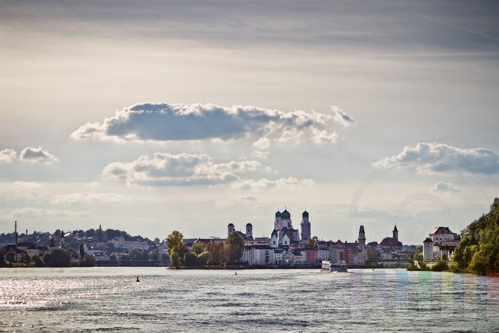 Blick von der Donau auf die historische Altstadt von Passau an einem spätsommerlichen Nachmittag. An der Baumgruppe in der Bildmitte fliessen Donau und Inn (links) zusammen. Die Mündung des 3. Passauer Flusses, der Ilz, liegt am rechten Bildrand hinter dem Turm