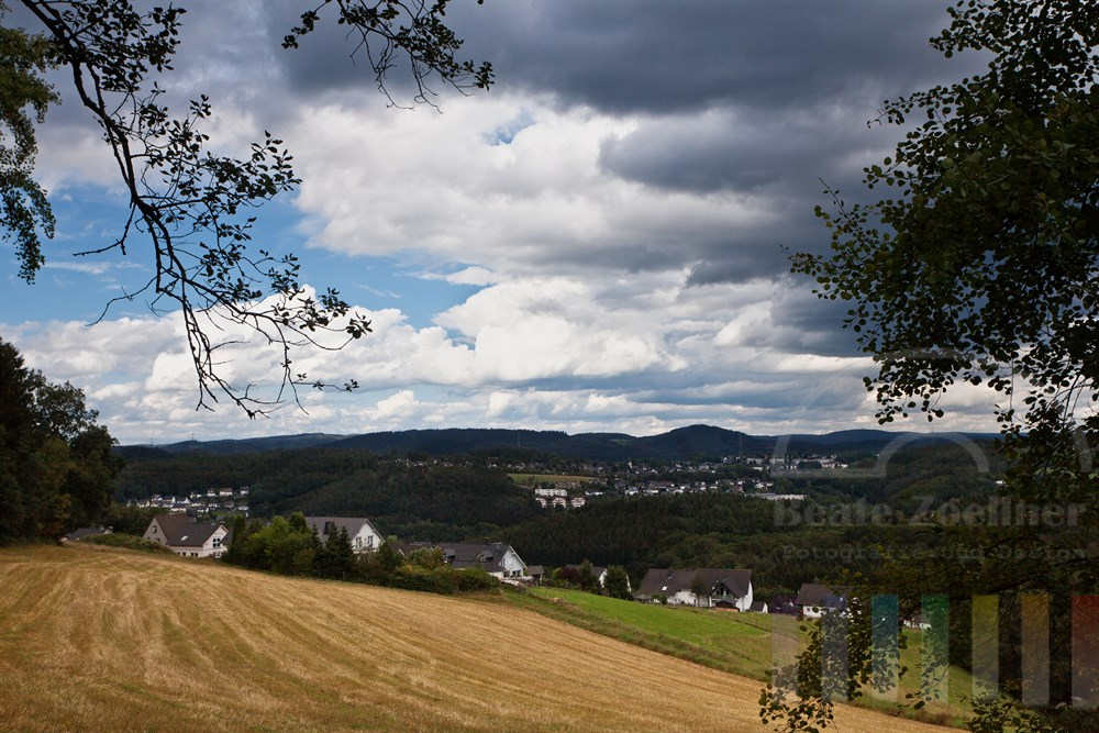 Blick von einem Waldrand ueber das spaetsommerliche Bergische Land bei Wiehl, Wolkenhimmel