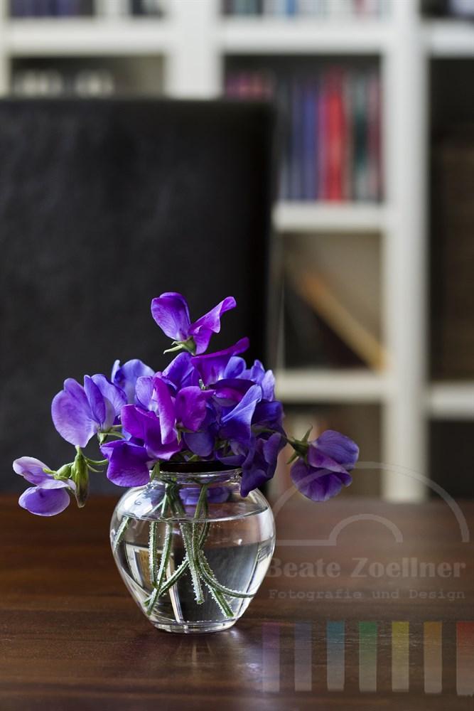 Kleine Vase mit lila blühenden Wicken auf einem Holztisch