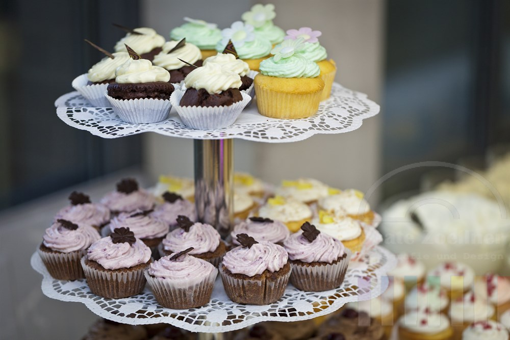 Bunt dekorierte Cupcakes auf einer Etagere auf einem Buffet