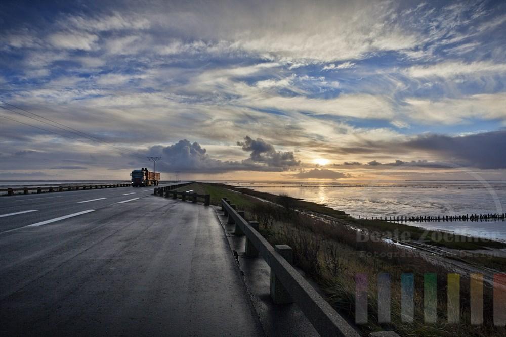 LKW faehrt vom daenischen Festland ueber den Strassendamm zur Insel Roemoe, Morgenstimmung. Links und rechts des Dammes liegt das Wattenmeer
