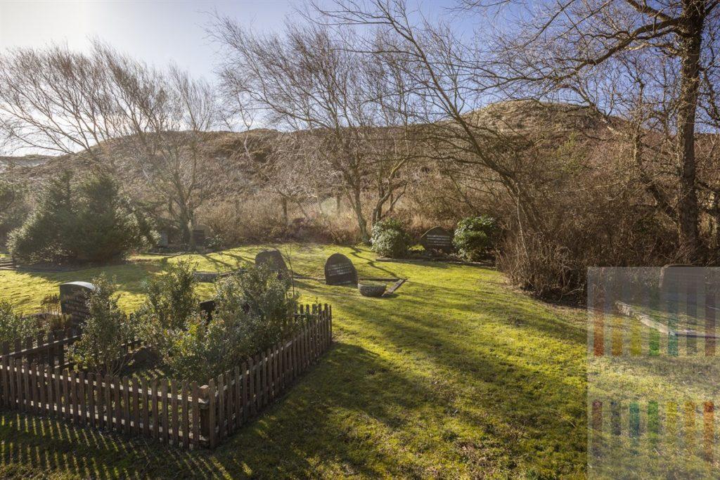 Wintersonne scheint auf Gräber auf dem idyllische gelegenen Dünenfriedhof in List auf der Insel Sylt